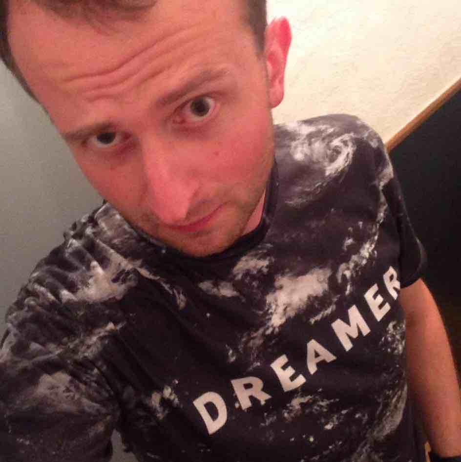 A photo of me: gazing into the camere in a Dreamer t-shirt.